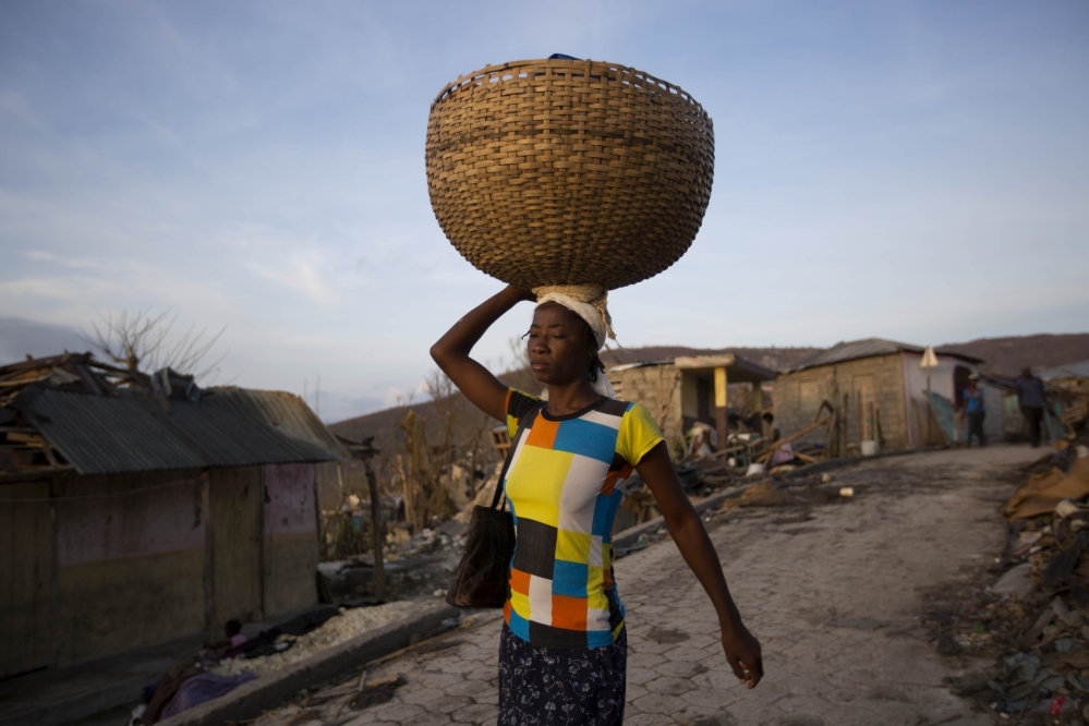 A woman walks as she sells bread near destroyed homes by Hurricane Matthew in Jeremie, Haiti on Monday, Oct. 10, 2016. Almost a week after Matthew's assault,  power is still out, water and food are scarce, and officials say that young men in villages along the road between the hard-hit cities of Les Cayes and Jeremie are putting up blockades of rocks and broken branches to halt convoys of vehicles bringing relief supplies. (AP Photo/Dieu Nalio Chery)