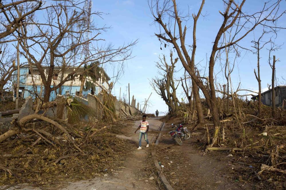 A man walks past the debris left by Hurricane Matthew in Haiti on Monday. Nearly a week after the storm hit, some communities have yet to receive any assistance. l