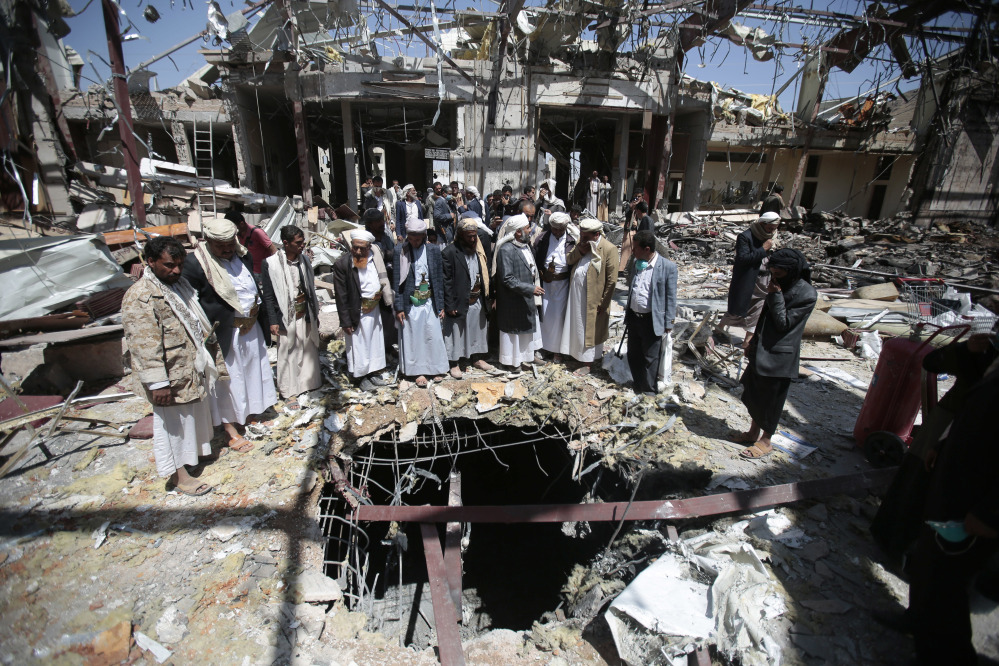 Members of the Higher Council for Civilian Community Organization inspect a destroyed funeral hall Thursday as they protest against a deadly Saudi-led airstrike on a funeral hall in Sanaa, Yemen. The attack led to missiles being fired at U.S. warships, which responded by destroying three coastal radar sites.