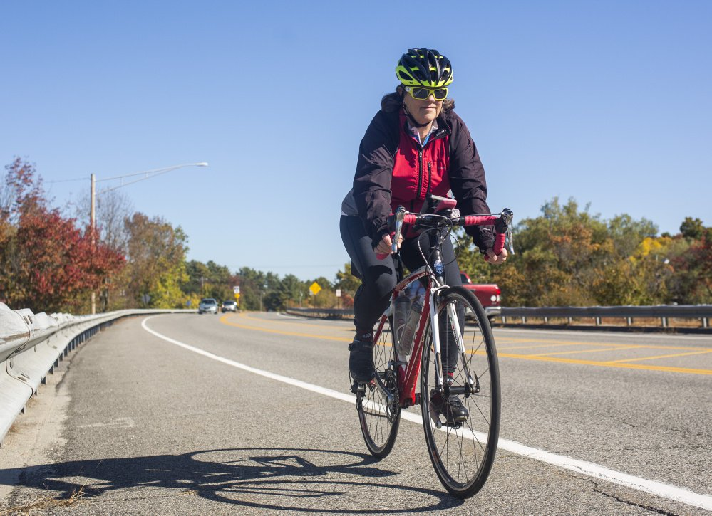 Sue Ellen Bordwell rides her bike on the Route 1 bridge in Yarmouth. Bordwell spends a lot of time advocating for biker and walker safety, and she has advocated for  improvements to the Route 1 bridge.