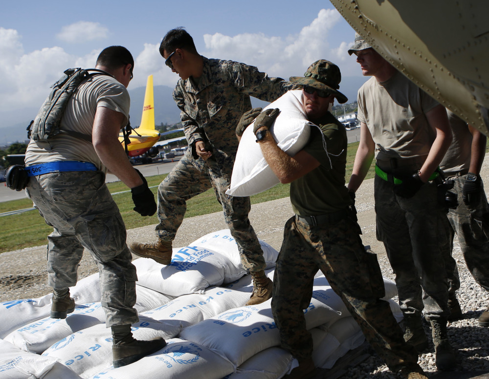 U.S. military troops load bags of rice for Hurricane Matthew relief in Port-au-Prince, Haiti, on Thursday.