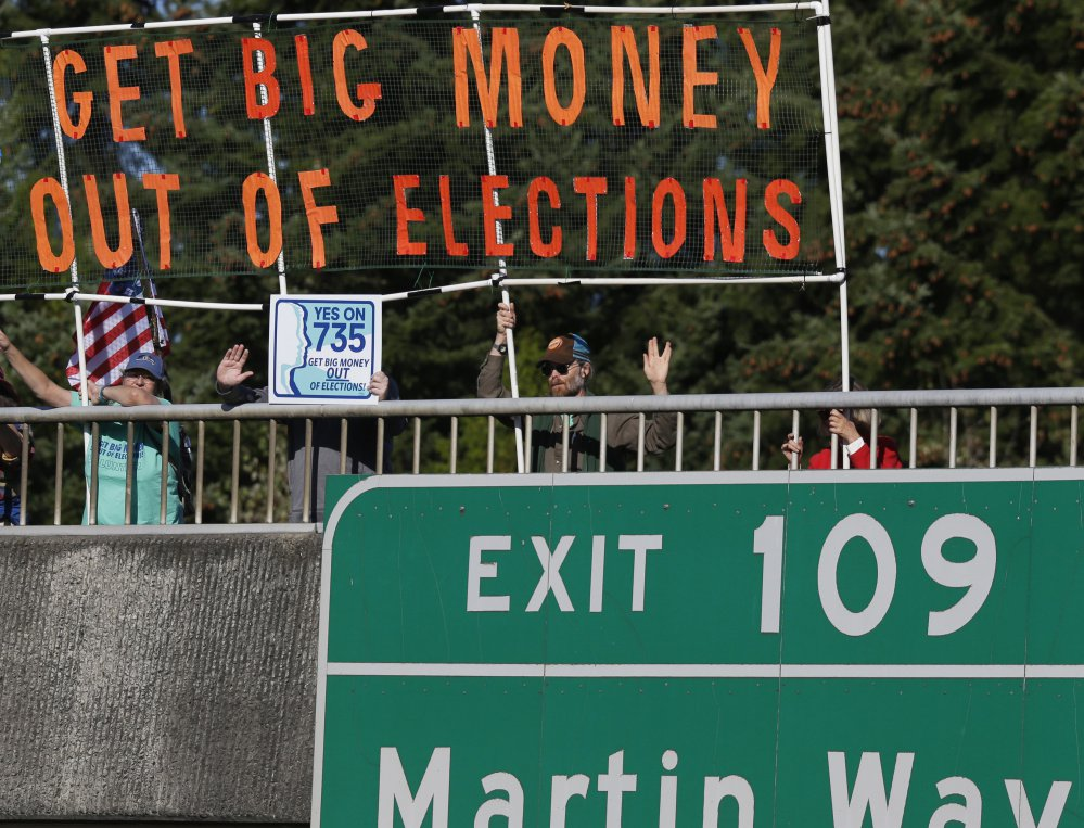 Supporters of an initiative in Lacey, Wash., hold a banner during the evening commute in Lacey, Wash., in September. Voters increasingly are upset with the way campaigns are paid for disproportionately by big-money donors