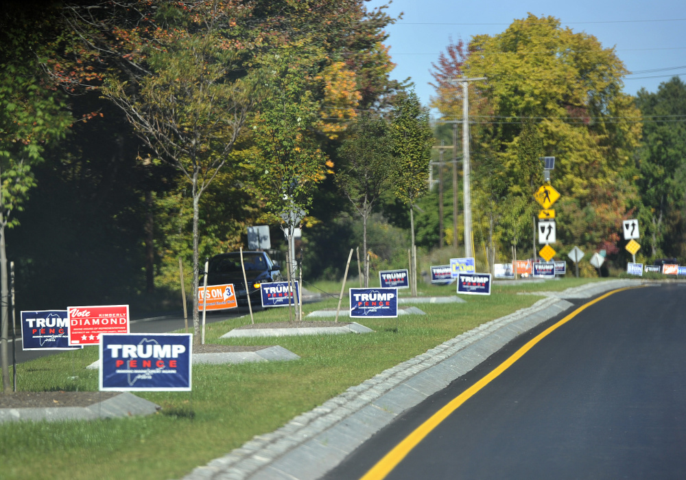 Political signs line a road in Falmouth on Thursday. Gov. Paul LePage asked the Maine Department of Transportation to notify campaigns if their signs violate a new law that requires signs be 30 feet apart and no bigger than 4 feet-by-8 feet.