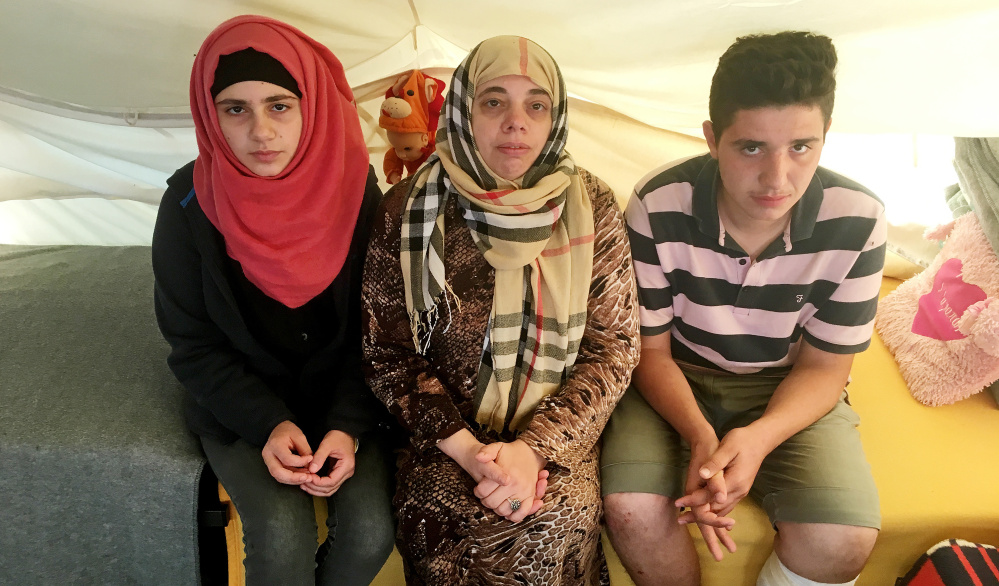 Lamis Wahed, center, sits with two of her four children, Rama, 16, left, and Kamal, 17. Stranded in Greece for seven months, they have applied for a program to resettle them elsewhere in Europe. But EU nations are reneging on their promises.
