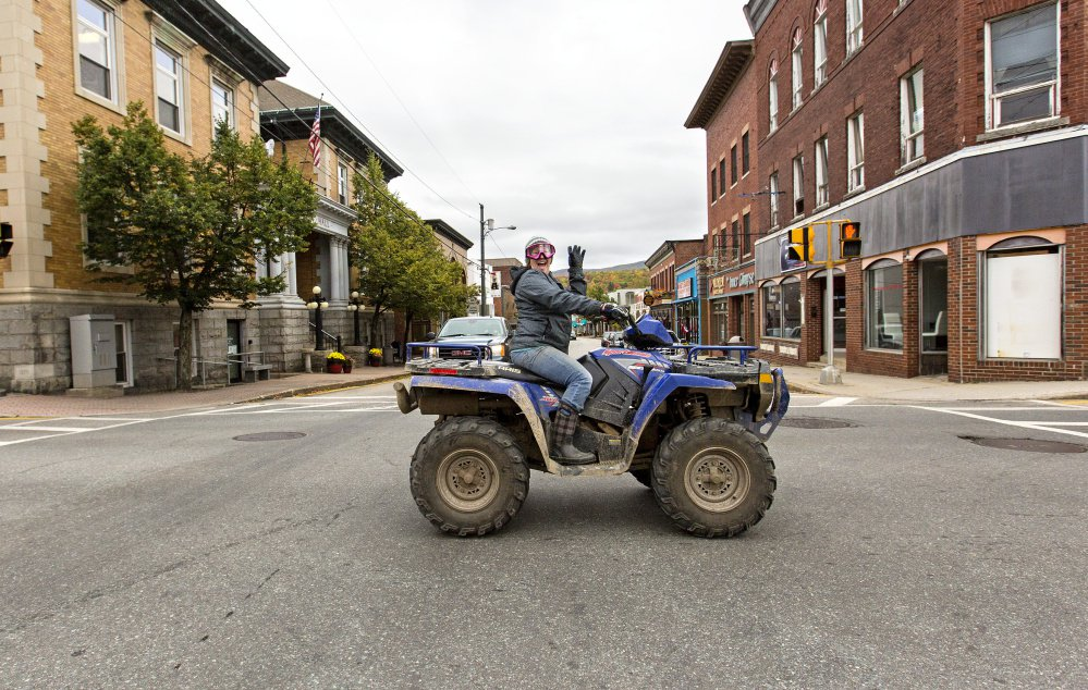 An ATV rider crosses Main Street in Berlin, N.H. The town has legalized ATV use on some public streets.