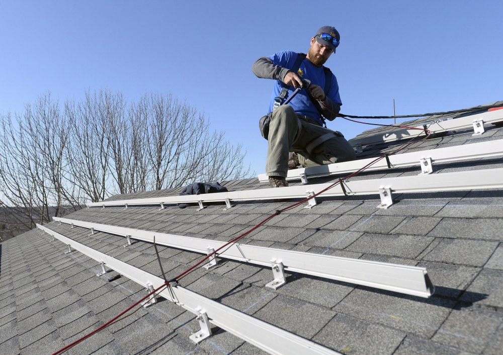 Zach Good of ReVision Energy prepares a roof for solar panels at a home in Cape Elizabeth last year. The cost of solar technology has fallen dramatically.