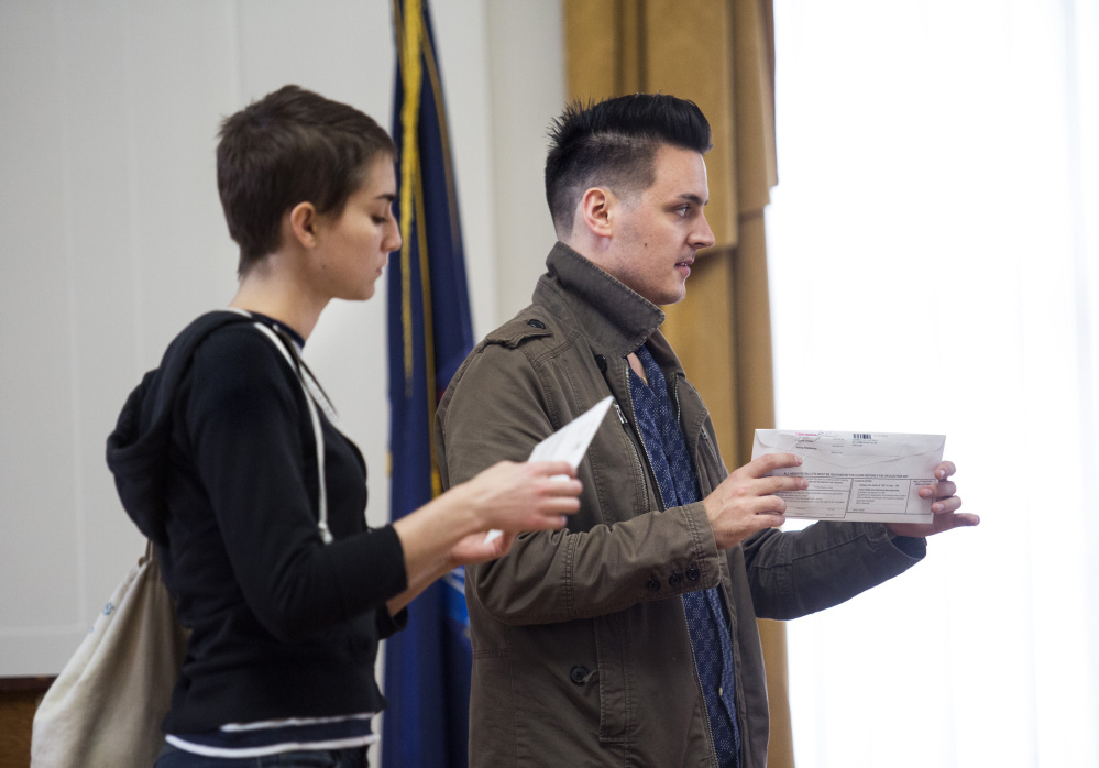 Kaila Moore and Justin Chamberlain of Portland seal their ballots after voting early at City Hall on Tuesday. Maine city clerks defended the electoral process Tuesday, saying their poll workers get hours of training to make sure voting goes smoothly and isn't marred by fraud.