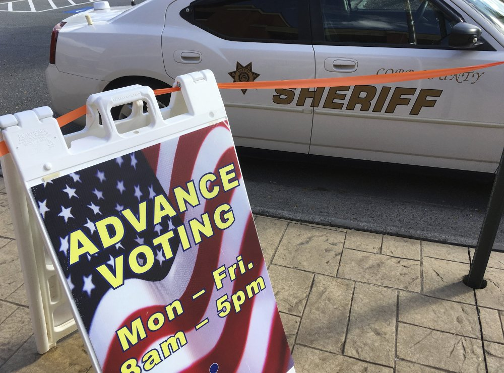 A sign displays absentee voting hours at a voting site in Marietta, Ga., as a Cobb County Sheriff's deputy sits in his vehicle Monday. Documented instances of voter fraud are extremely rare.
