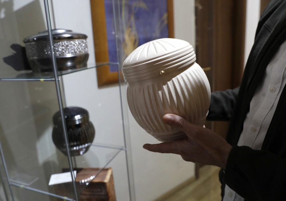 A man holds an urn at a funeral parlor in Rome on Tuesday, when the Vatican published guidelines for Catholics who want to be cremated, saying their remains cannot be scattered, divvied up or kept at home but rather stored in a sacred, church-approved place.