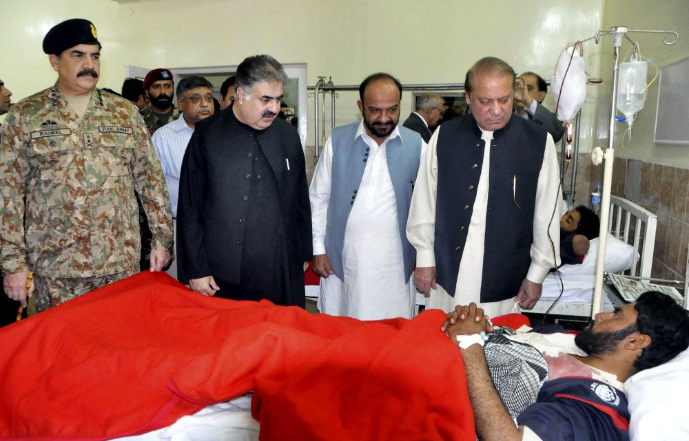 Pakistan's Prime Minister Nawaz Sharif, right, talks to a survivor of an overnight attack on the Police Training College, with army chief Gen. Raheel Sharif, left, at a hospital in Quetta on Tuesday.  Associated Press