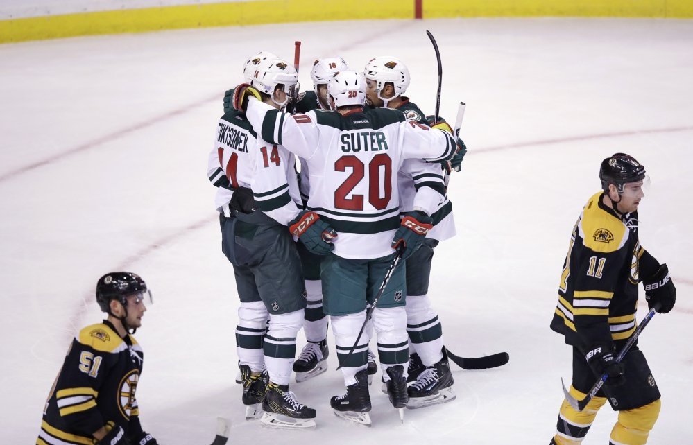 Minnesota right wing Jason Pominville is surrounded by teammates after scoring a third-period goal in the Wild's 5-0 shutout of the Bruins on Tuesday night in Boston.