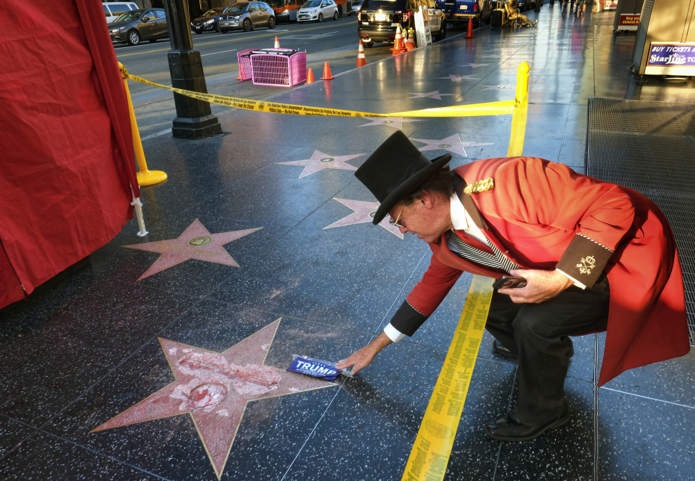 Gregg Donovan, who calls himself the unofficial ambassador of Hollywood, places a sticker for Republican presidential candidate Donald Trump on Trump's vandalized star on the Hollywood Walk of Fame on Wednesday in Los Angeles.
