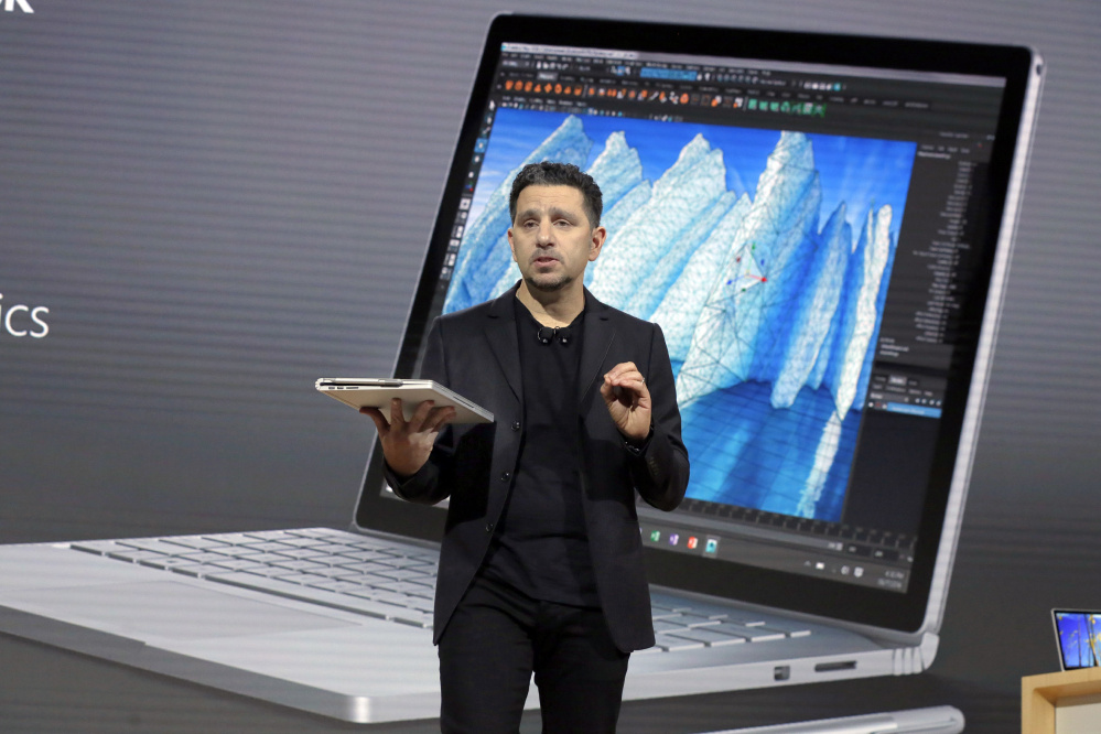 """Panos Panay, Microsoft's vice president of devices, displays an updated Surface Book at a media event Wednesday in New York. """"We want ... to help everyone create,"""" he said."""