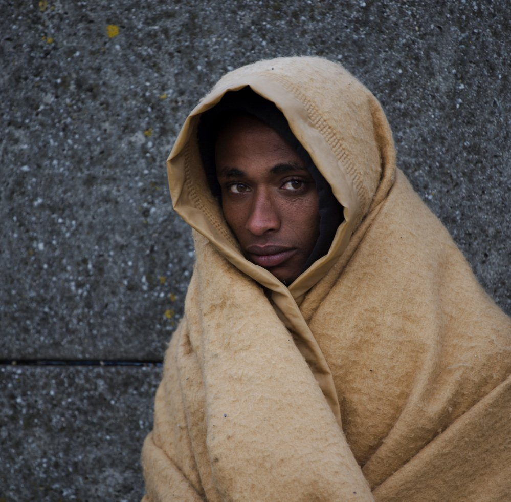 """An Eritrean migrant forced from """"the jungle"""" in northern France waits for transport to a new home now that the camp has been razed."""