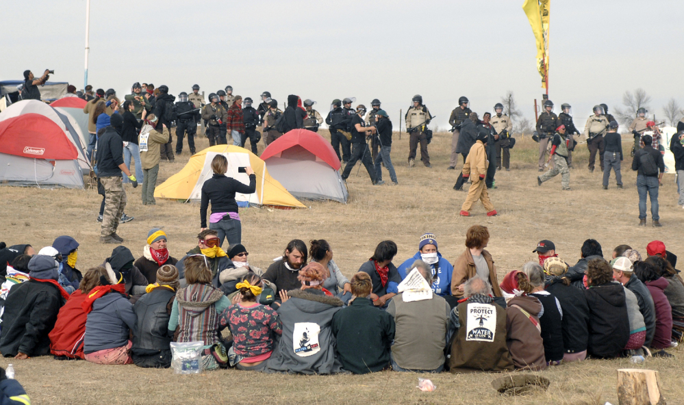 Dakota Access pipeline protesters sit in a prayer circle as law enforcement officers make their way across the camp to remove them in North Dakota on Thursday.