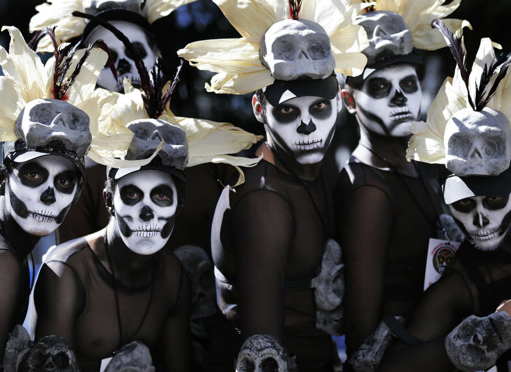 Men wait for a Day of the Dead parade to begin in Mexico City on Saturday. Traditional Day of the Dead celebrations are changing under the influence of Hollywood movies.