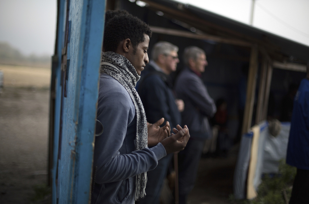"""A migrant prays during the final service at a makeshift church in what remains of the squalid camp near Calais, France, on Sunday. French authorities are evacuating residents of the so-called """"jungle"""" camp and razing its tents and shanties."""
