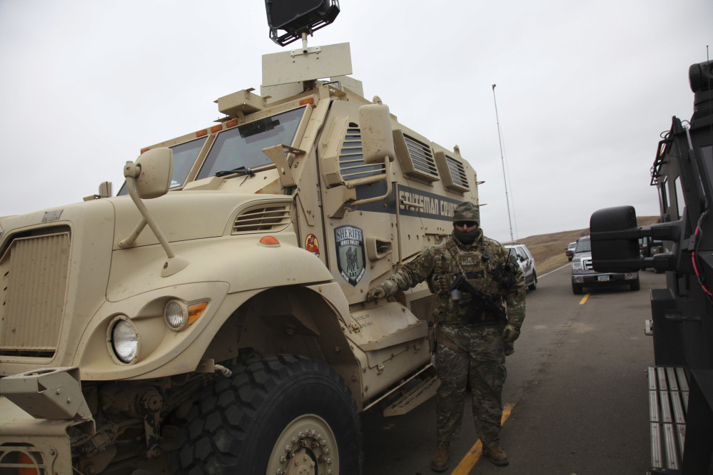 A member of the Stutsman County SWAT team stands guard by an armored personnel carrier equipped with a long range acoustic device, while deployed to watch protesters demonstrating against the Dakota Access pipeline in Cannonball, N.D., on Sunday.