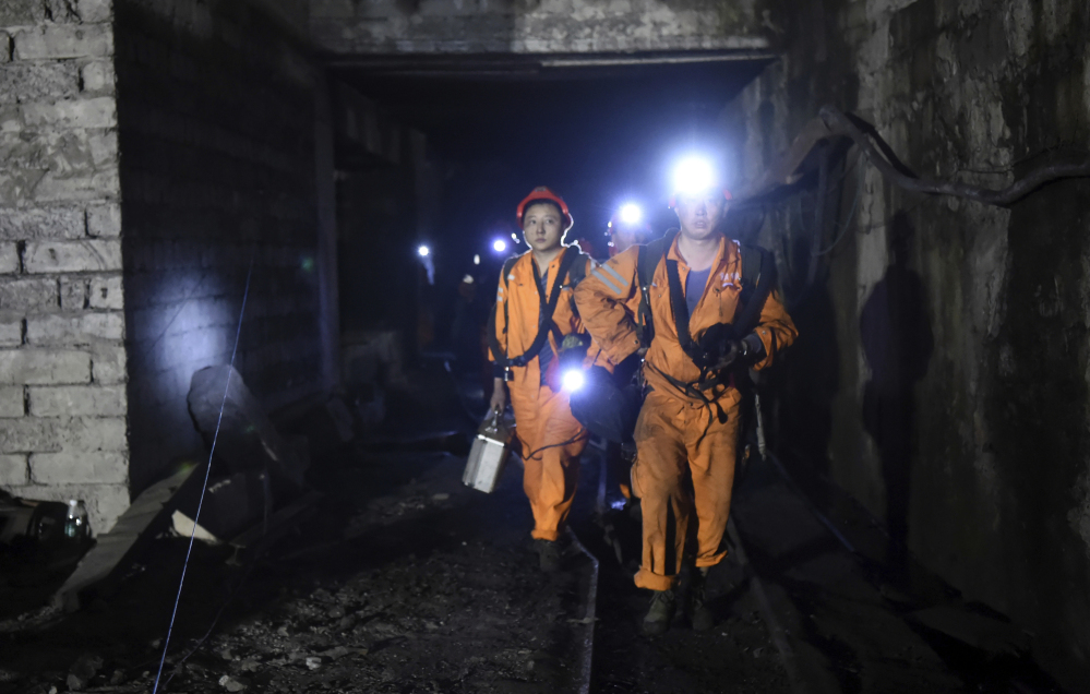 Rescuers work Monday at the Jinshangou Coal Mine in Chongqing, southwest China, where a gas explosion killed more than a dozen workers. Hundreds of rescuers were hindered by debris as they worked through the night trying to find another 20 miners.