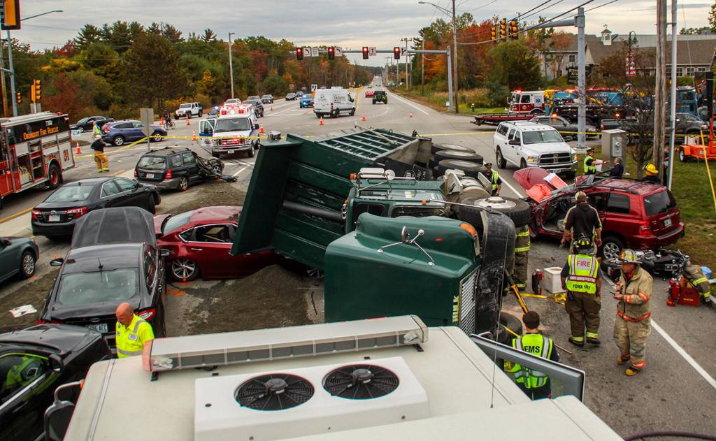 Emergency personnel work at the scene of a 10-vehicle accident Thursday in York. The accident happened when a dump truck filled with gravel tipped onto its side. AJ St. Hilaire/Portsmouth Herald via AP