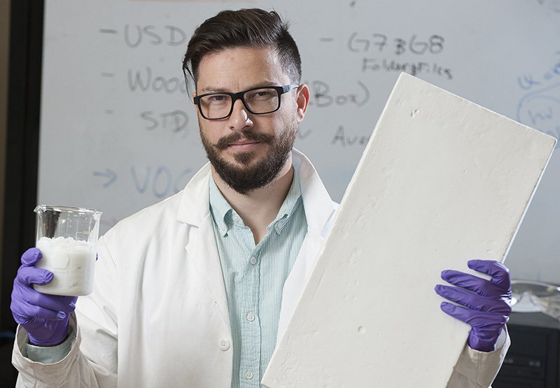 Nadir Yildirim holds a wood and water slurry in one hand and a sample insulation board made from the slurry in the other at his lab at the University of Maine.