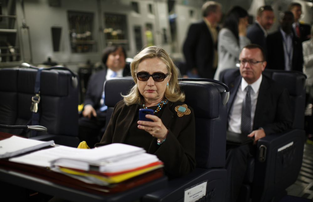In this 2011 file photo, then-Secretary of State Hillary Clinton checks her Blackberry from a desk inside a C-17 military plane.