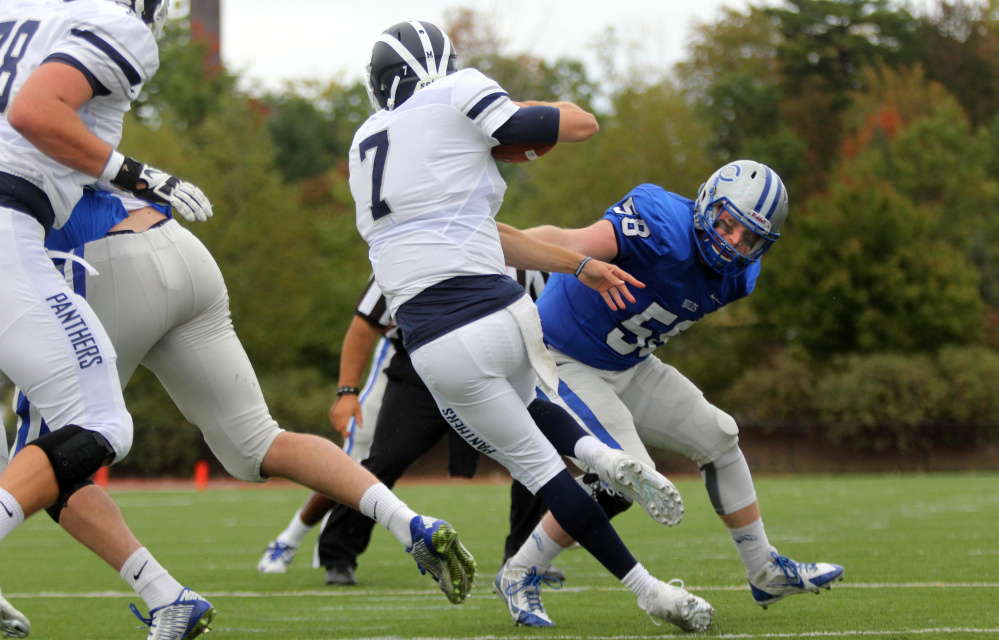 Middlebury College quarterback Jared Lebowitz eludes a tackle by Colby College's Ben Hartford during first-half action Saturday in Waterville.