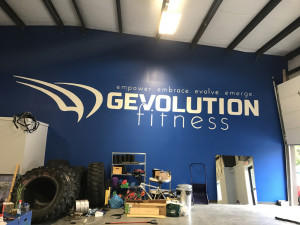 A large GEvolution Fitness logo and inspirational words adorn the wall Saturday on the gym's new facility on Edison Drive in Augusta.