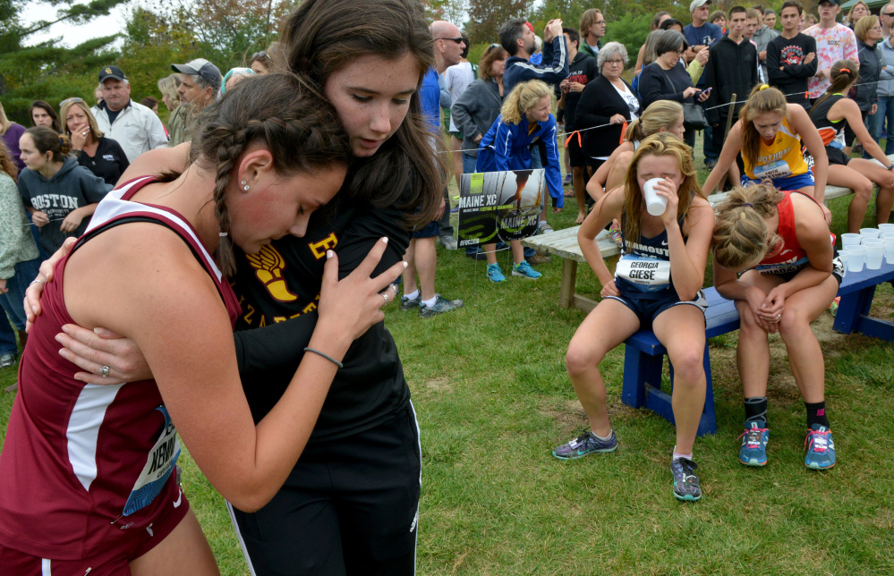 Cape Elizabeth High School's Kelsey Kennedy, far left, is comforted by a teammate following her race at the Festival of Champions on Saturday in Belfast.