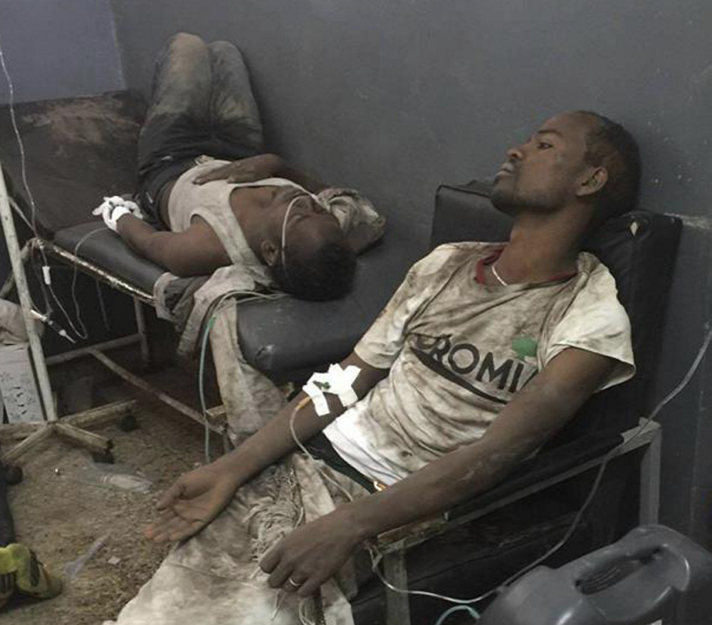 Men receive medical attention after a stampede at the religious festival. Dozens of people were crushed to death Sunday.