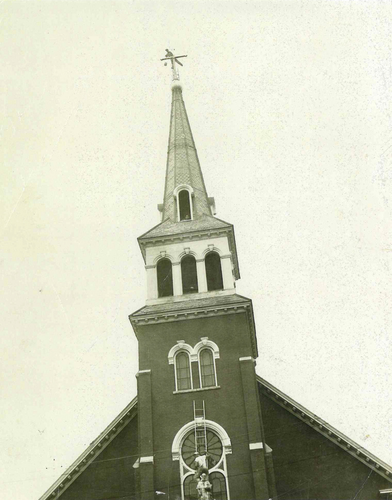 """Joseph Armand """"Blackie"""" Roy paints the cross atop the steeple of the former St. Francis de Sales Catholic Church on Elm Street in Waterville in this 1964 photo. The church was torn down in 2013 and replaced with senior housing."""