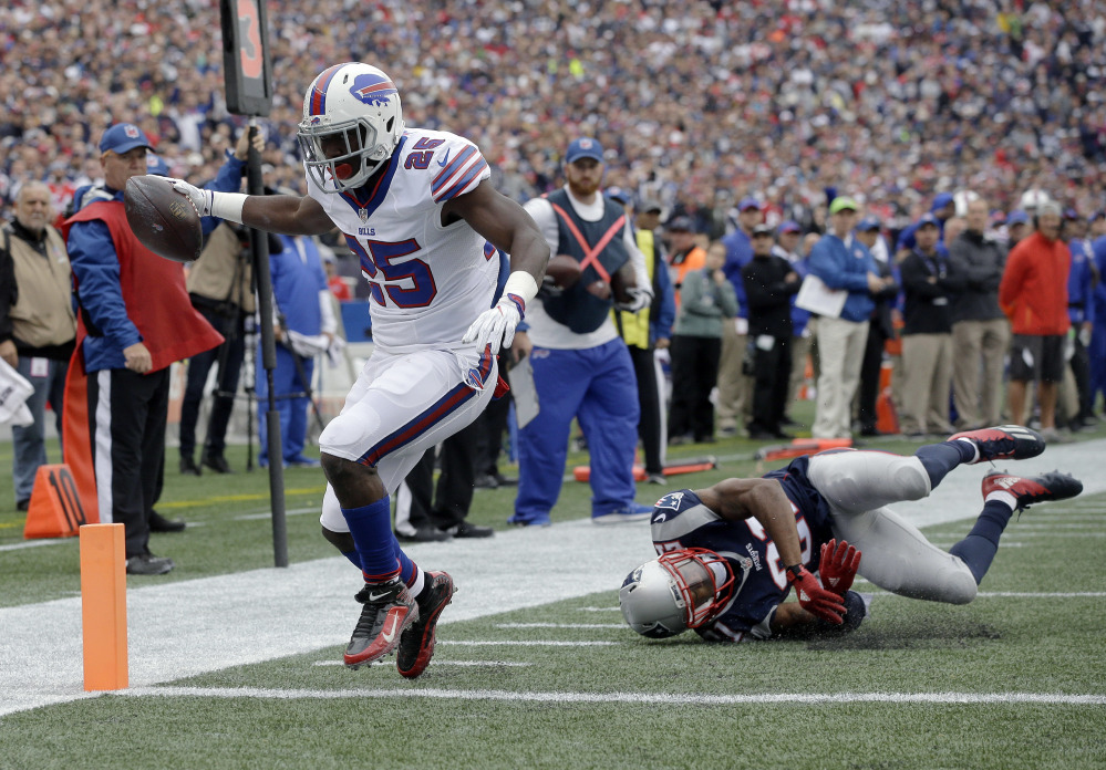 Buffalo Bills running back LeSean McCoy (25) leaves New England Patriots cornerback Malcolm Butler, right, tumbling as he crosses the goal line for a touchdown Sunday in Foxborough, Massachusetts.