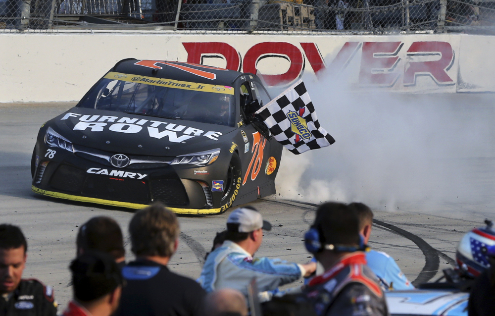 Martin Truex Jr. holds the checkered flag as he does a burnout after winning a NASCAR Sprint Cup Series race Sunday at Dover International Speedway in Dover, Delaware. Kyle Busch (18) was second.