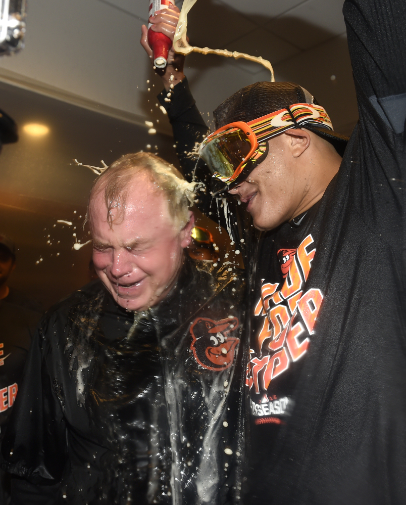 Baltimore Orioles manager Buck Showalter is doused with beer by Manny Machado in the visitors' clubhouse after the Orioles defeated the New York Yankees 5-2 to go to the playoffs Sunday in New York.