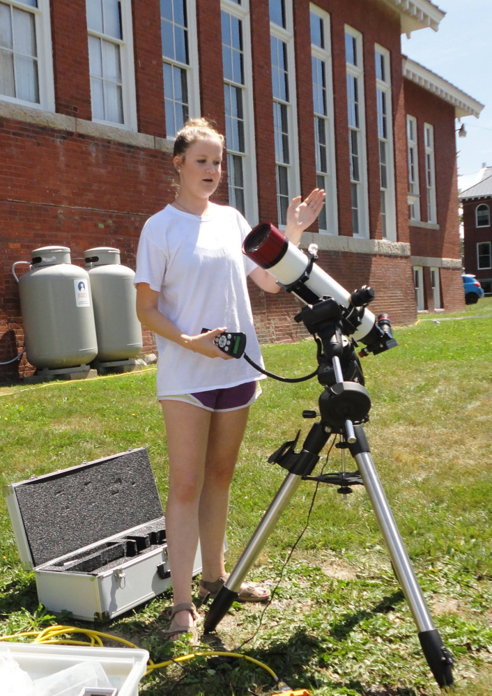 Summer museum intern Kinsley Subers explains the telescope use for visitors.