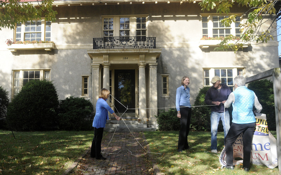 Genie Gannett, left, unknots a rope that Rebecca Lazure, second from left, Denis Thoet and Susan Gross used to hang a sign Monday for the First Amendment Museum in front of the Gannett House in Augusta. Gannett serves as chairman and president of the board, Lazure serves as executive director, and Gross and Thoet are on the board.