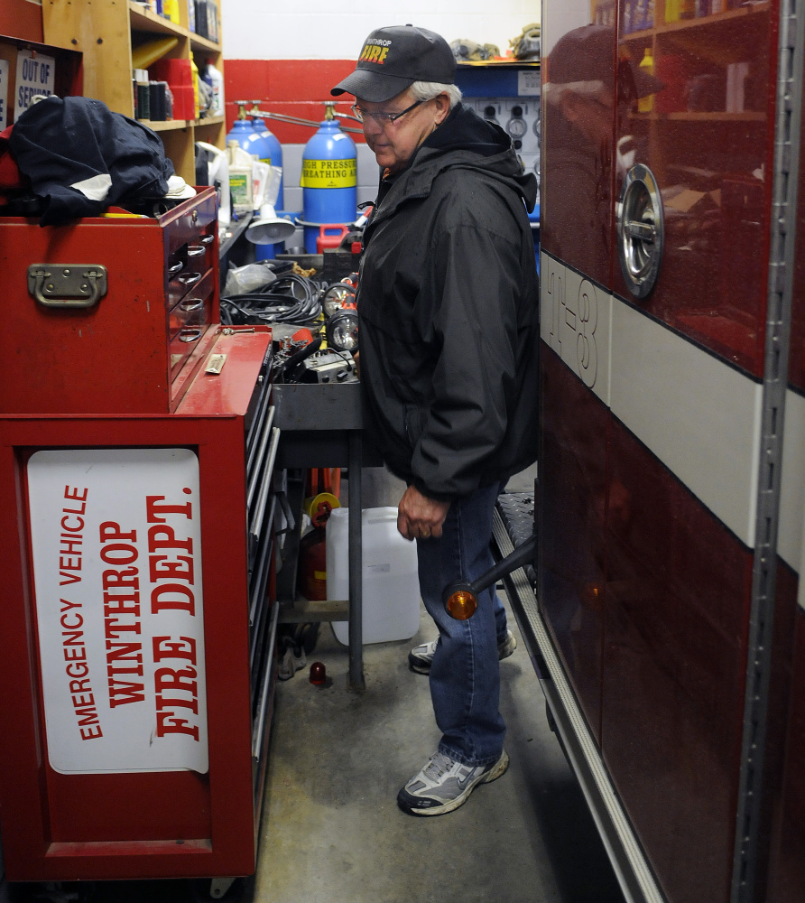 Winthrop Fire Dept. Deputy Chief Dave Currie squeezes between a work area and engine on April 12 at the town's station.