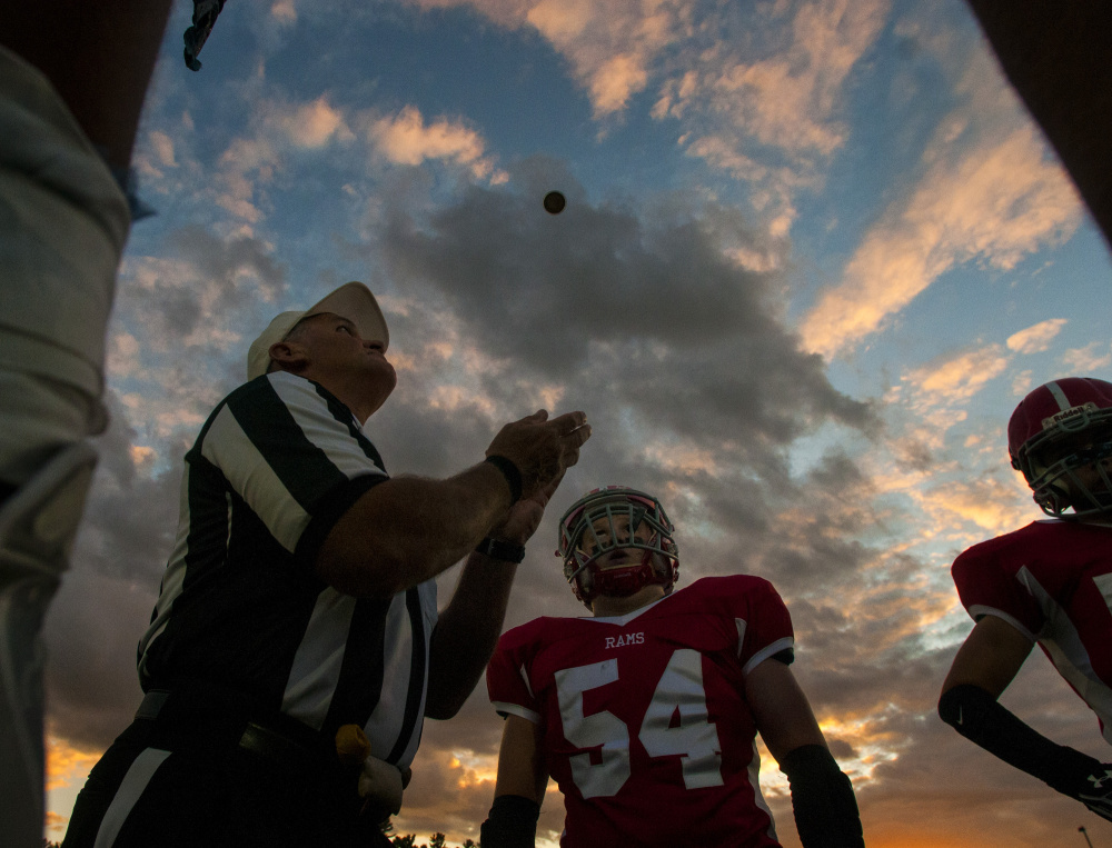 Staff file photo by Joe Phelan   Referee Jerry Norton prepares to catch a tossed coin at Alumni Field in Augusta prior to the start of a game betwee Mt. Blue and Cony last month. The Cougars and Rams are fighting for a playoff berth in ultra-competitive Pine Tree Conference Class B.
