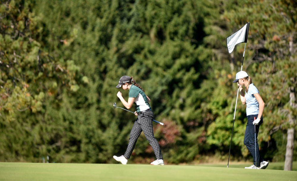 Carrabec's Katie Dixon, center, celebrates her putt on the ninth hole as Greta Freiburger, of Dirigo, holds the flag during the Mountain Valley Conference qualifier Wednesday at Natanis Golf Course in Vassalboro.