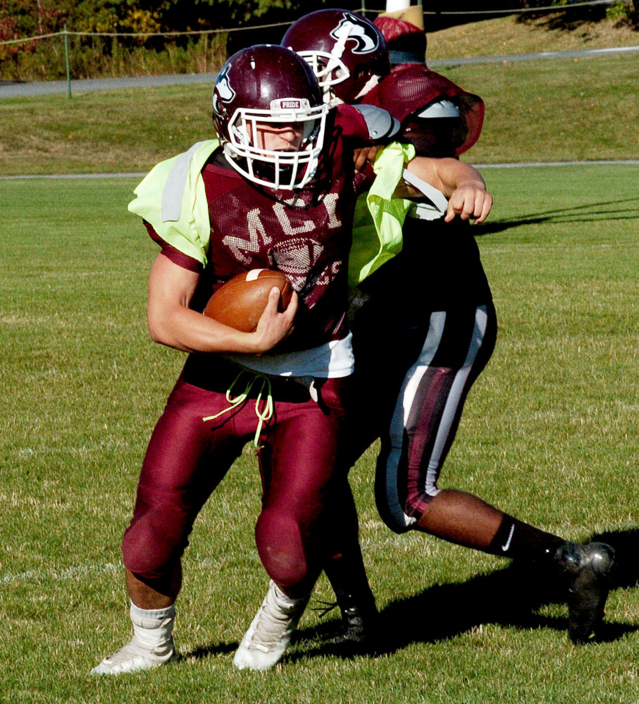 MCI running back Adam Bertrand evades a tackle during practice in Pittsfield on Wednesday.