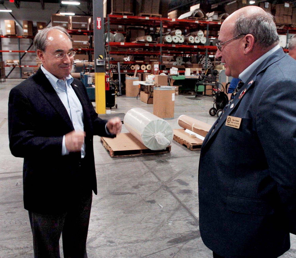 U.S. Rep. Bruce Poliquin, R-2nd District, left, speaks with Tim Gallant during a press conference at Auburn Manufacturing on Aug. 30.
