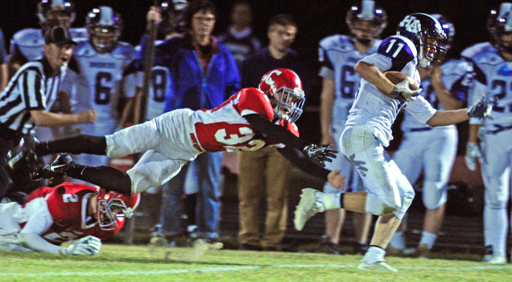 Cony's Michael Wozniak, left, dives after Hampden's Tyler Knights during a Pine Tree Conference B game Friday in Augusta.