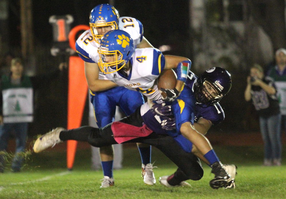 Waterville Senior High School's Cooper Hart tackles Belfast's Stan Sturgis in the backfield for a loss during first-half action Friday night in Waterville.