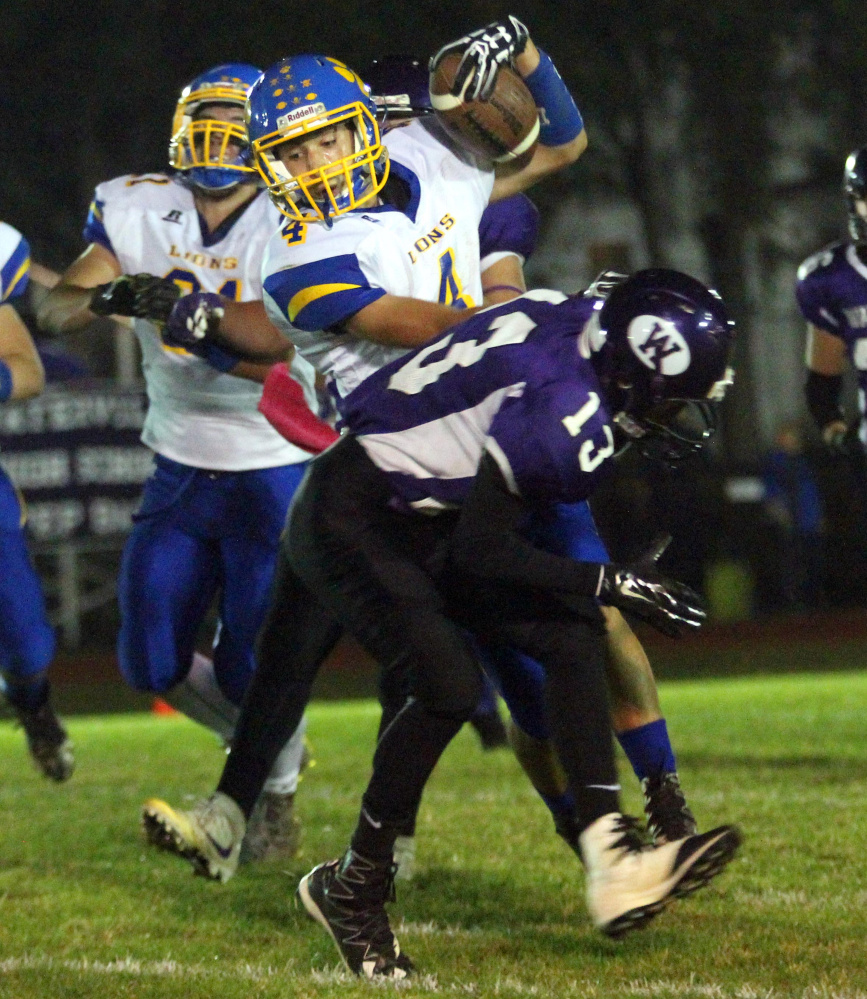 Belfast's Stan Sturgis fights off would-be Waterville tackler Gabriel Bohner during first-half action Friday night in Waterville.