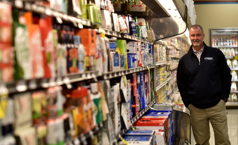 Jay Gould, manager of Tradewinds Market Plus on Hinckley Road in Clinton, stands in the market's beer section Thursday.