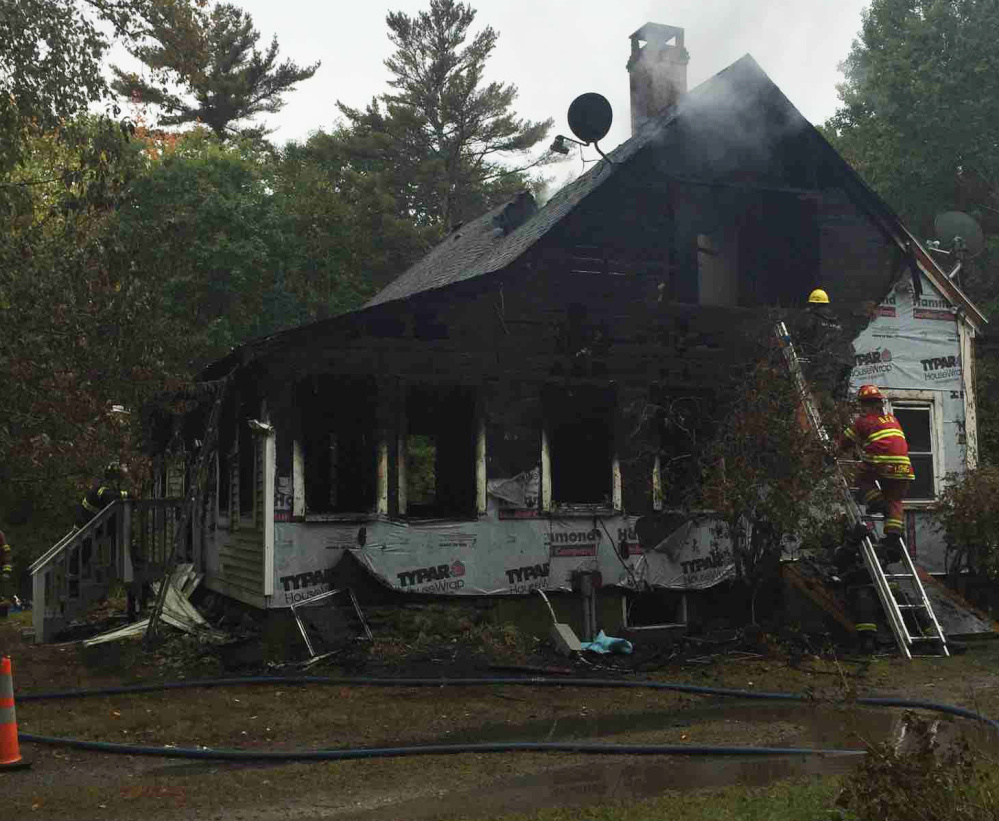 Firefighters try to put out a fire at 116 Pleasant Cove Road in Boothbay on Sunday morning. Two people died and four others injured.