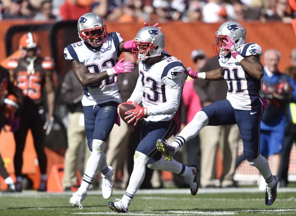 Patriots strong safety Patrick Chung celebrates an interception against the Cleveland Browns with Devin McCourty, left, and Jonathan Jones, 31, in the second half Sunday at Cleveland. Associated Press/David Richard