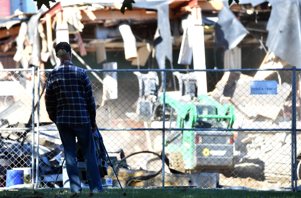 Raymond LaPointe watches and records on video the demolition of the former Levine's building in downtown Waterville on Thursday.