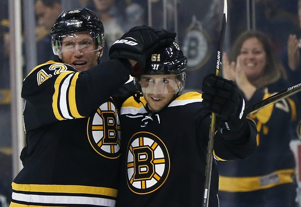 Boston Bruins forward Ryan Spooner (51) celebrates his winning goal with teammate David Backes during overtime of a preseason game against the Flyers in Boston on Saturday.