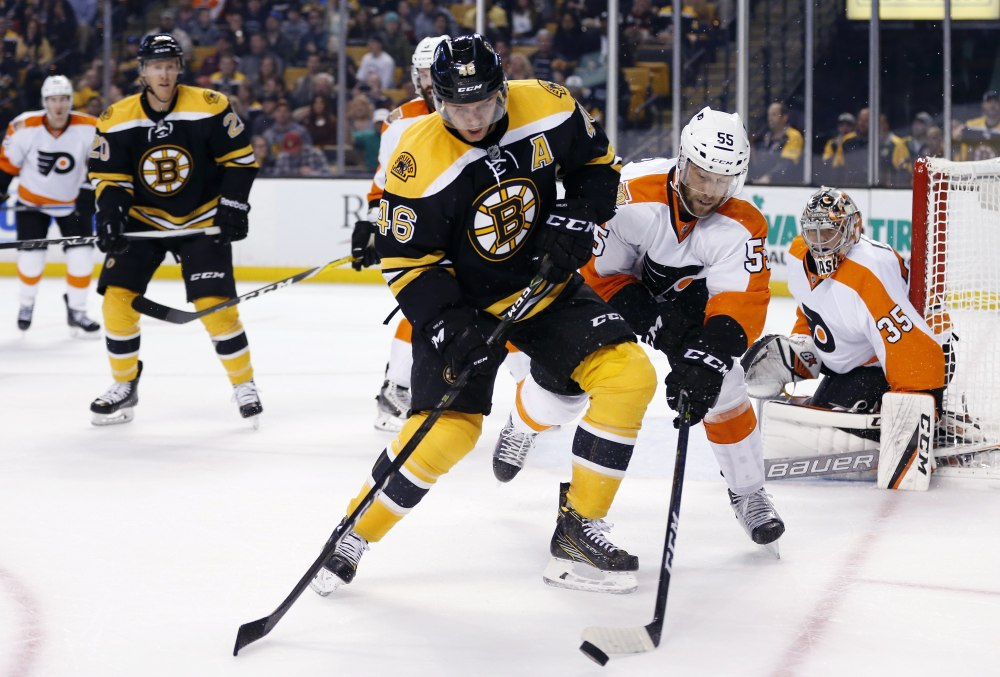 Boston Bruins forward David Krejci (46) and Philadelphia's Nick Schultz battle for the puck during the second period of a preseason game in Boston on Satruday.